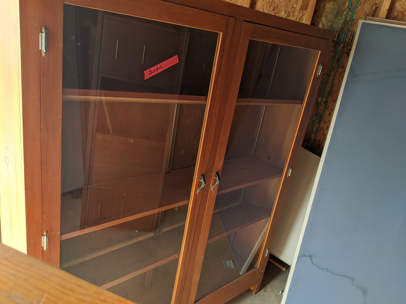Reddish wood cabinet with glass doors