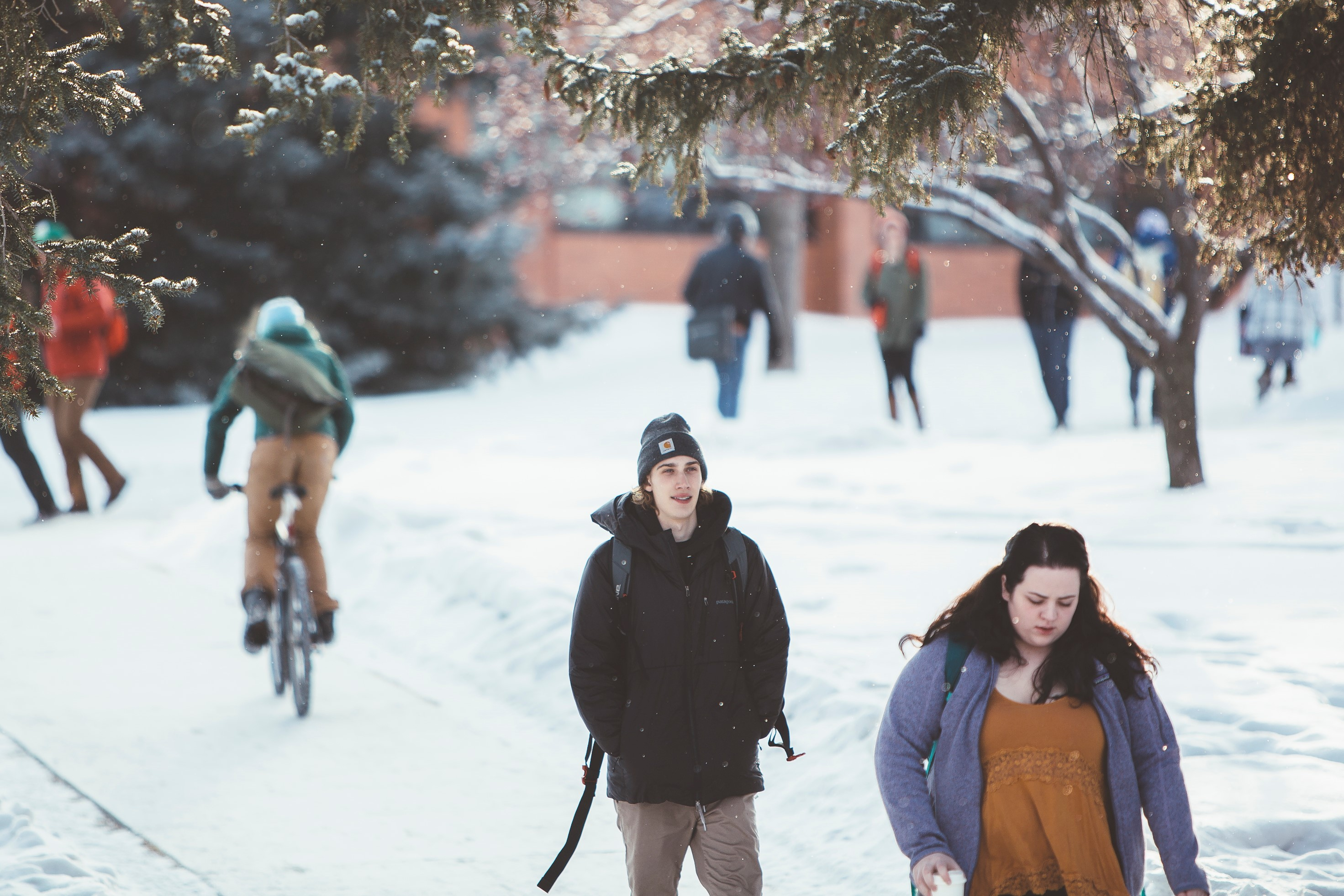 Students walking on campus in light snow.