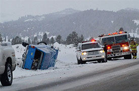 overturned vehicle on snowy roadway with first responders on site