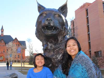 Elva and her daughter Rebbeca sitting next to the bobcat statue in front of Montana and Leon Johnson Halls