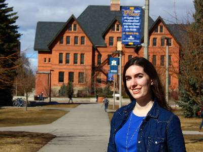 Kailyn is in a blue shirt and jean jacket in front Montana Hall with MSU and What It Takes banner overhead.