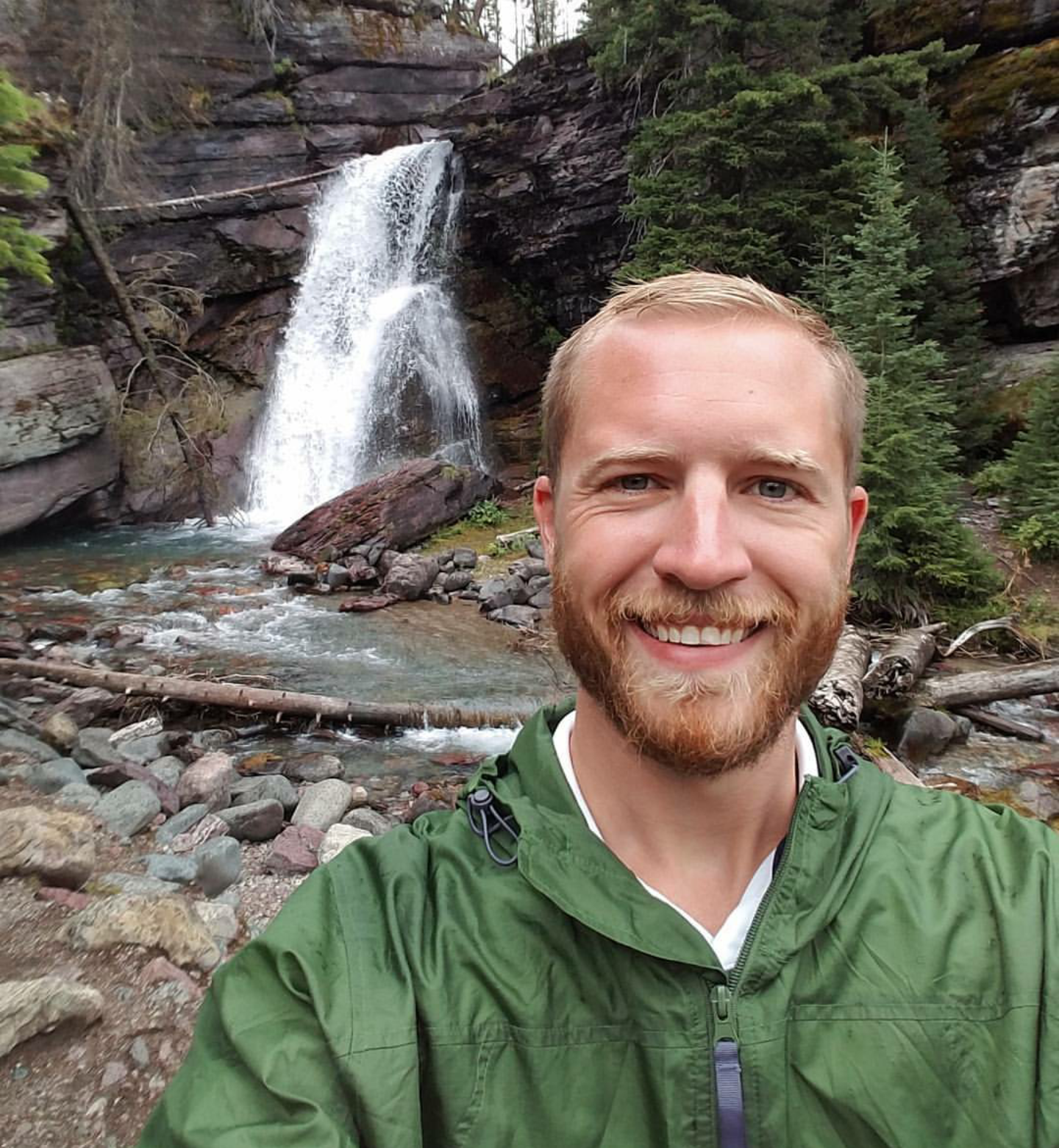 Mark Hedinger in a green jacket in front of a waterfall