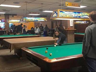 Students playing pool in the SUB Rec Center. A girl is taking a shot, while a boy watches.