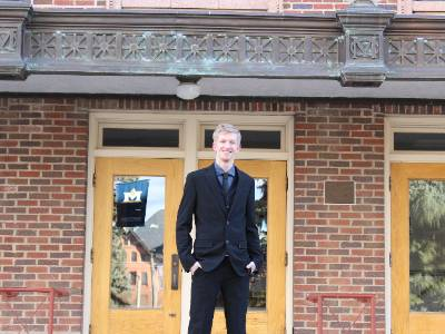 Wade is in a black suit standing outside of a brick building. The door has a reflection of the MSU banner.