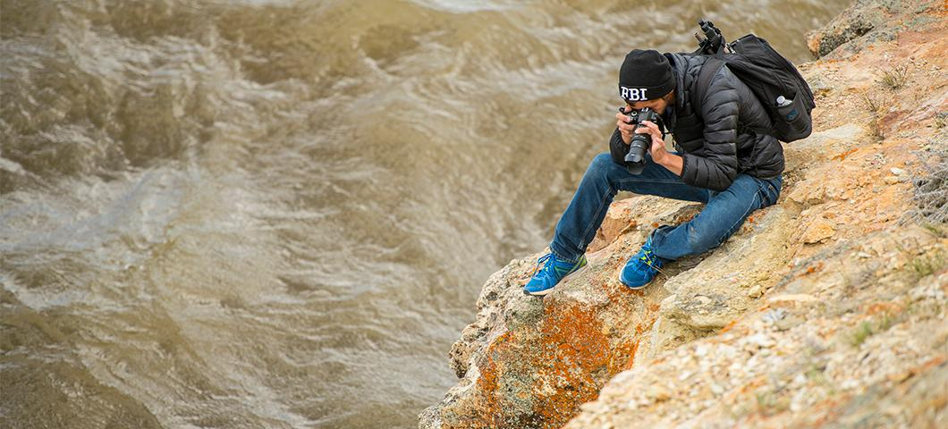 A student photographing from a rock perched over a river
