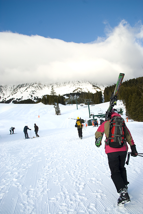 Skiers walk up a mountain