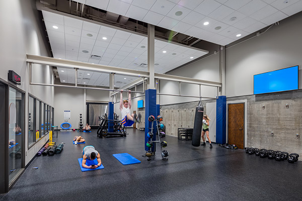 Fitness area in a gym with weights, mats, and a heavy bag