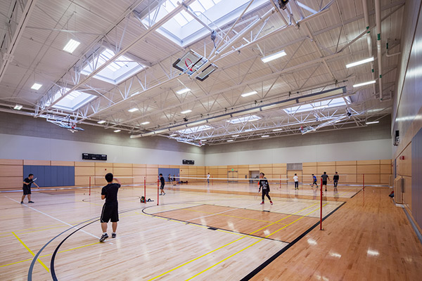 Wood court gym with users playing racquet sports