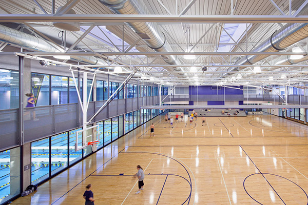 Overhead shot of a wood court gym with users playing basketball