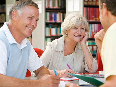 Older adults conversing with an instructor at the library
